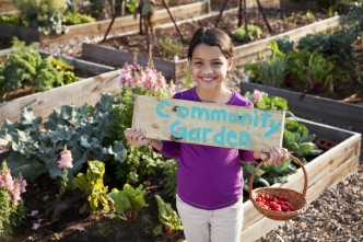 Image of girl holding community garden sign
